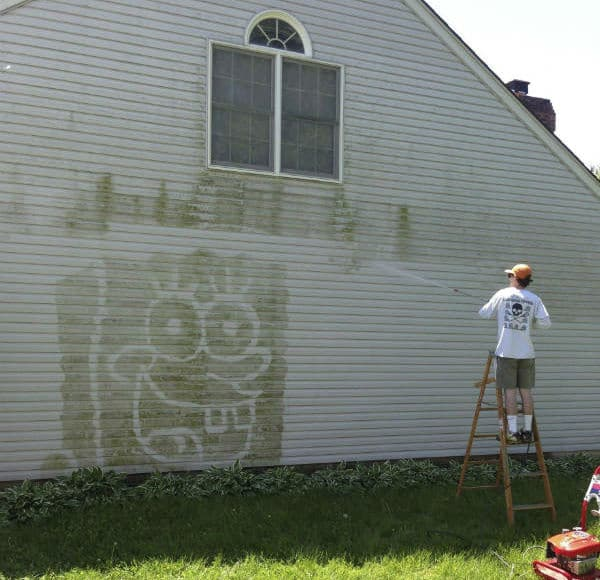 Power washing house with ladder and goofy drawing