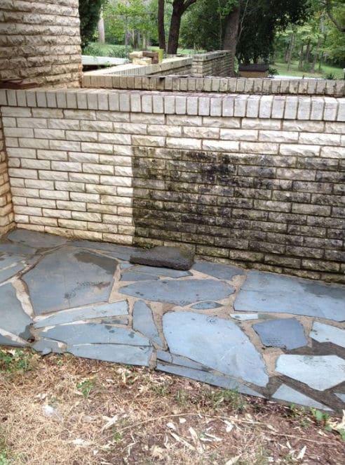 Pressure washing a brick wall